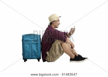 Traveler Sitting Against A Suitcase And Using Cellphone