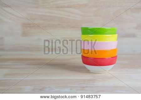 Colorful Ceramic Bowls Stacked On Each Other On Wood Background With Copy Space