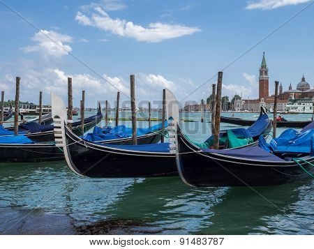 Venice, Italy - 21 May 2105: Gondolas Moored On The Lagoon, With The Church Of San Giorgio Maggiore