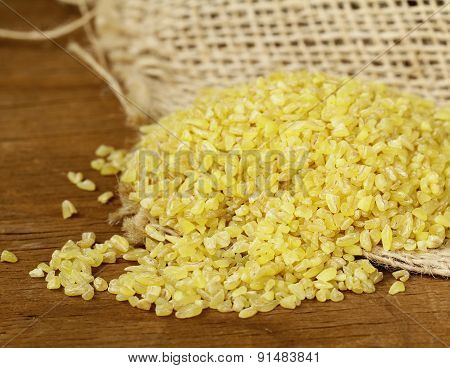 yellow natural grain bulgur on a wooden table
