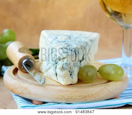 piece of blue cheese with green grapes on a wooden board