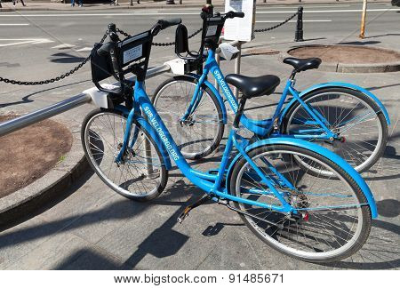 Blue City Bicycles For Rent Stand On A Parking