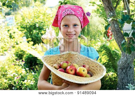 Little Girl Is Standing With Basket Of Apples In The Apple Orchard