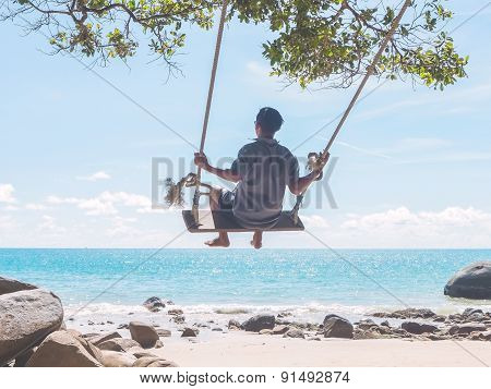Young Man Swinging On The Beach
