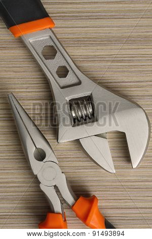 Adjustable Wrench And Pliers Closeup On Wooden Background