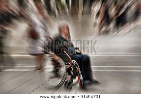 Abstract Background. A Disabled Person In A Wheelchair On A City Street. Radial Zoom Blur Effect