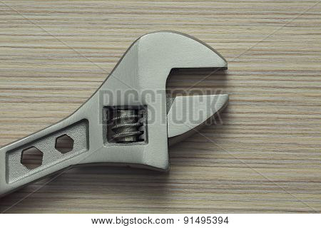 Adjustable Wrench Closeup On Wooden Background