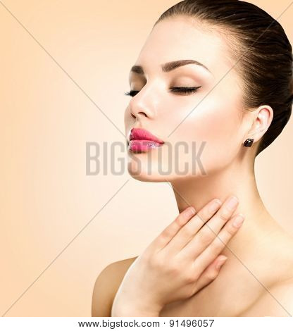 Beauty Portrait. Beautiful Spa Woman Touching her Face. Perfect Fresh Skin. Pure Beauty brunette Model. Youth and Skin Care Concept. Studio shot