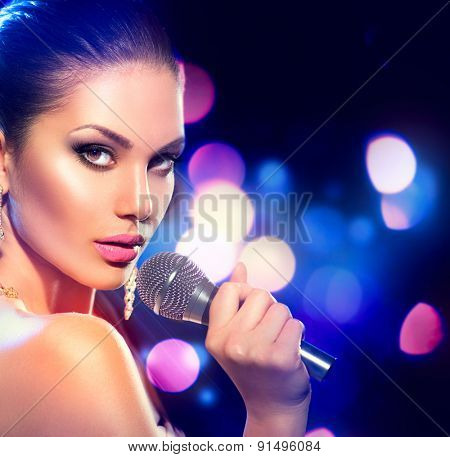 Beautiful Singing Girl. Beauty Glamour fashion Woman with Microphone over Blinking bokeh night background. Glamour Model Singer. Karaoke song. Karaoke party