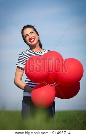 Happy young woman with a red balloon on a green meadow