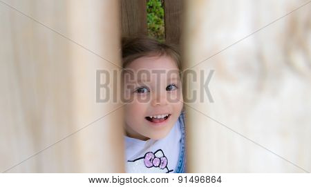 Child Laughs Hidden Behind A Fence