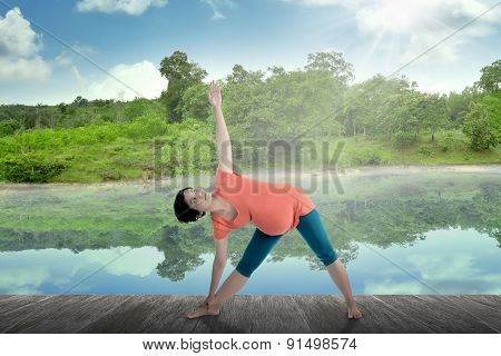 Pregnant Mother Doing Yoga At The Lake