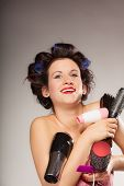picture of hair curlers  - Young woman preparing for date having fun cute girl with curlers styling hair with many accessories comb brush hairdreyer on gray - JPG
