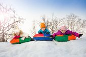 stock photo of row trees  - Row of children sliding down on the tubes together during beautiful winter day with trees trunks on the background - JPG