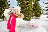 foto of snowball-fight  - Cute girl ready to throw snowball while standing behind the snow wall with fir forest on the background during beautiful winter day - JPG