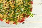 foto of italian parsley  - Italian pasta fusilli with fresh garlic and rocket leaves spanish chorizo parsley parmesan cheese on gingham plate white wood background - JPG