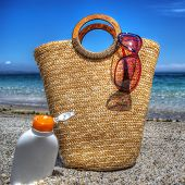 image of suntanning  - straw bag and suntan lotion by the sea - JPG