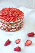 stock photo of strawberry  - Homemade delicious birthday strawberry sponge cake decorated with fresh strawberries on white kitchen table background - JPG