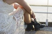 stock photo of woman boots  - Back of a blond woman wearing white lace dress and short black boots looking to the lake enjoying sun. Fashion for young people.