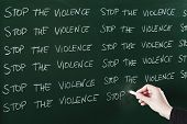 stock photo of punishment  - Stop the violence sentence written repeatedly on blackboard as a punishment - JPG