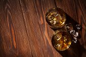 foto of whiskey  - Glasses of whiskey with ice on wooden table - JPG