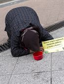 stock photo of begging  - An old woman is begging on the ground of a main street in Budapest Hungary - JPG