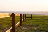stock photo of stockade  - Close up view of wooden fence in grassy landscape  - JPG