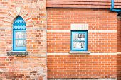 foto of lace-curtain  - Red brick wall with two contrasting blue windows with lace curtains - JPG