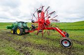 stock photo of tractor  - The tractor with new hay tedder standing in the field - JPG
