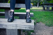 image of woman boots  - A young woman wearing boots is sitting on a bench in a park - JPG