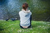image of water bird  - A young woman is watching the birds as she is resting by the water in a park - JPG