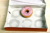 stock photo of donut  - empty cakes box with only one tempting and delicious donut with toppings left in unhealthy nutrition and sugar and sweet cake addiction concept - JPG