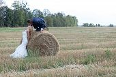 stock photo of she-male  - Beautiful married couple acting very romantic on a field of bales - JPG