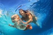 stock photo of mother baby nature  - In blue pool young mother swimming with happy baby son  - JPG