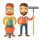 pic of hand-barrow  - A two smiling gardener carries a plant in wheelbarrow and holding a rake - JPG