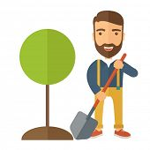 stock photo of shovel  - A happy gardener planting a tree in his yard using shovel - JPG