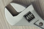 image of extreme close-up  - adjustable wrench closeup on wooden background - JPG