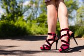 foto of ankle shoes  - Beautiful female legs in pink shoes walking along the road - JPG