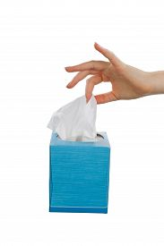 stock photo of tissue box  - Female hand picking facial tissue from blue napkin box - JPG