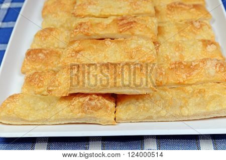 Homemade cheese crackers on white platter on a blue placemat with pattern blocks