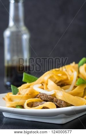 Chinese food. Beef chow mein. Black stone background