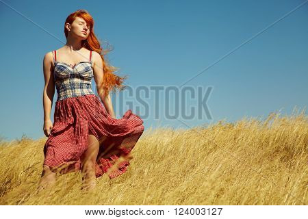 sexy redhead woman in a dress outdoors. Beautiful stylish romantic young girl on nature background. field and clear cloudless sky