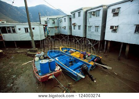 HONG KONG, CHINA - FEB 11: Abandoned boats in dried river of old fishermen village Tai O with rustic metal blocks on February 11, 2016. Hong Kong dollar is the eighth most traded currency in the world