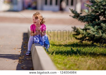 Beautiful sad little girl crying on summer background. cranky