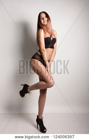 leggy slim beautiful sexy girl in a bra and black lace panties on a high heels, posing.