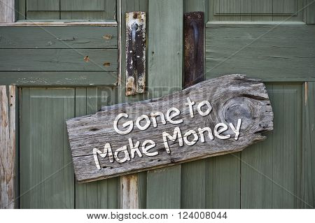Gone to make money sign on old green doors.