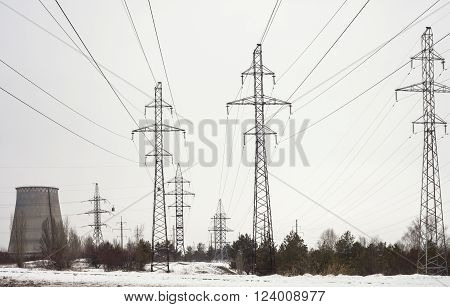 Electricity pylons power lines and cooling tower of the power plant near Kyiv (Ukraine) in winter.