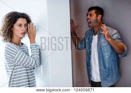 Woman listening to man screaming on opposite sides of the wall
