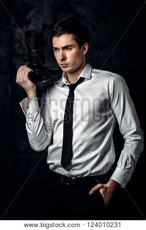 Serious professional photographer in a white shirt with a tie