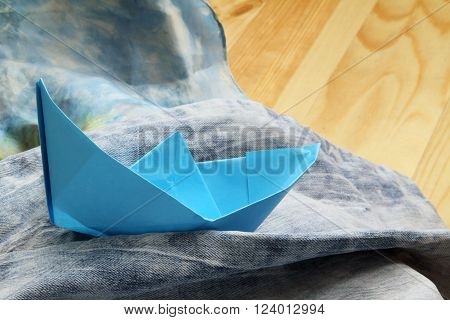 paper boat floating on the waves of denim shorts